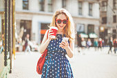Beautiful, blonde woman is checking the messages on her smart phone while she is drinking coffee