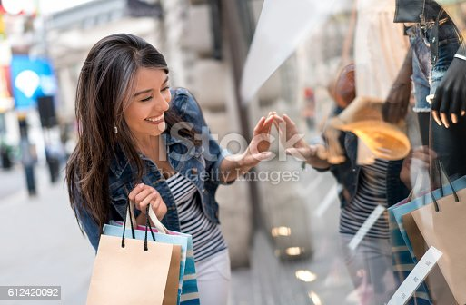 Very happy Latin American shopping woman looking at a window and smiling