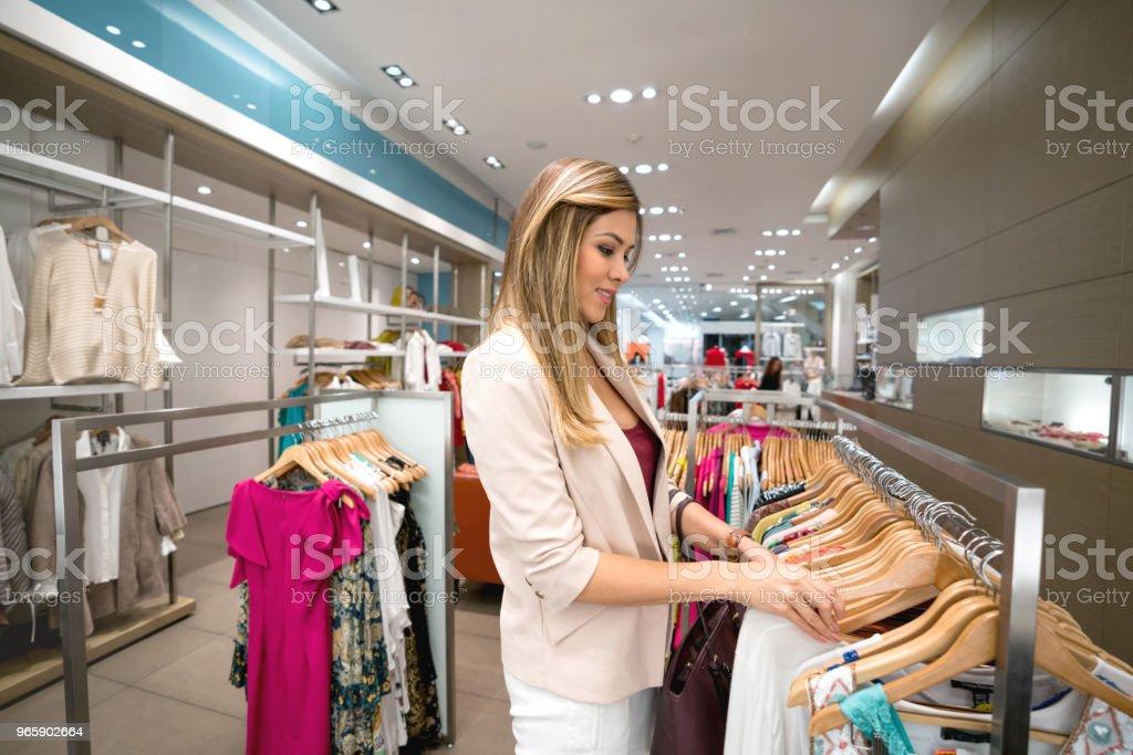 Winkelen vrouw kijkt kleding in een winkel - Royalty-free 20-29 jaar Stockfoto
