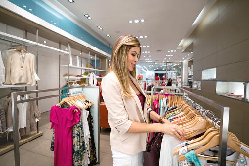 Winkelen Vrouw Kijkt Kleding In Een Winkel Stockfoto en meer beelden van 20-29 jaar