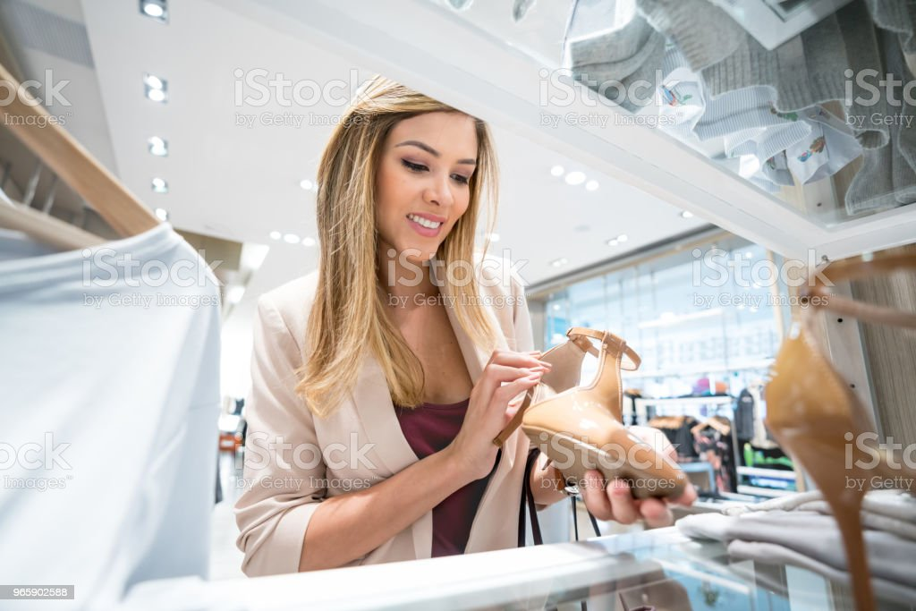 Vrouw op zoek naar schoenen in een kledingwinkel winkelen - Royalty-free 20-29 jaar Stockfoto