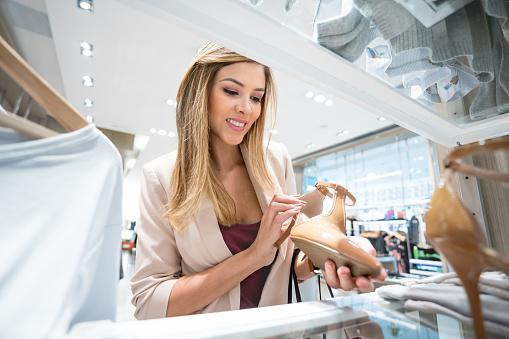 Vrouw Op Zoek Naar Schoenen In Een Kledingwinkel Winkelen Stockfoto en meer beelden van 20-29 jaar