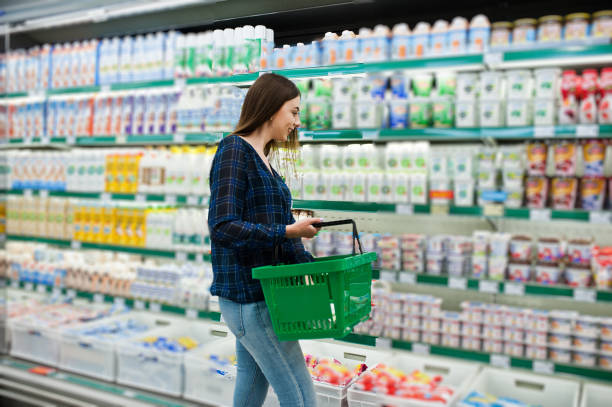 Shopping woman looking at the shelves in the supermarket stock photo