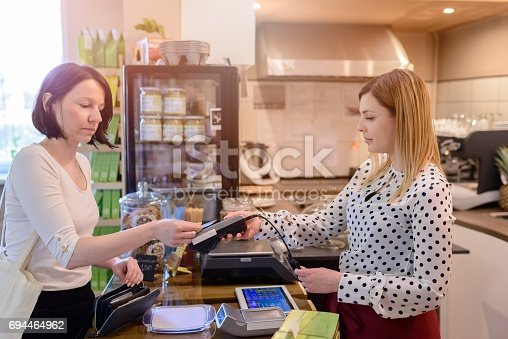 istock Shopping woman paying with credit card 694464962