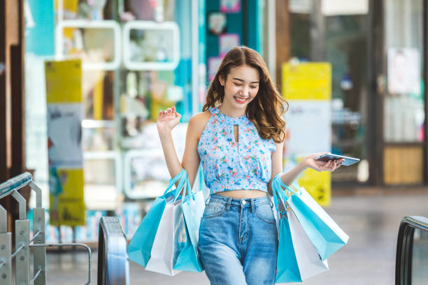 Shopping woman Lifestyle shopping concept, Young happy smiling asian woman with mobile phone and paper bag wearing crop top and jean in shopping street, vintage style thailand mall stock pictures, royalty-free photos & images