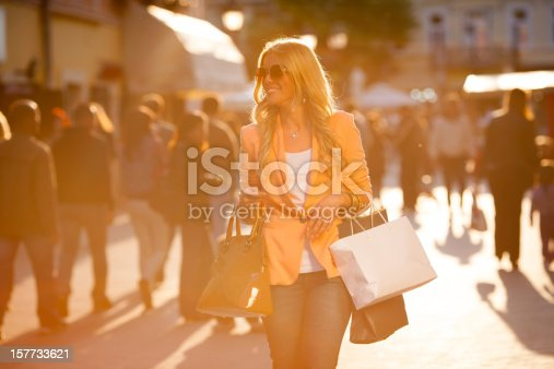 Smiled modern woman walking trough the city street with the shopping bags.