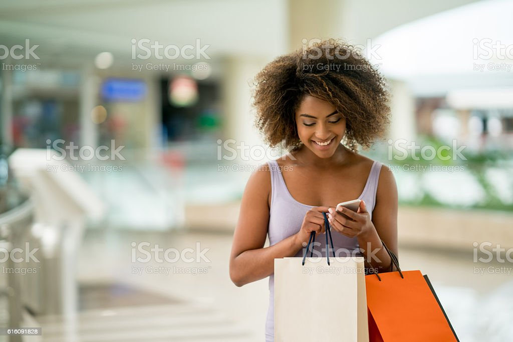 Shopping woman texting on her phone stock photo