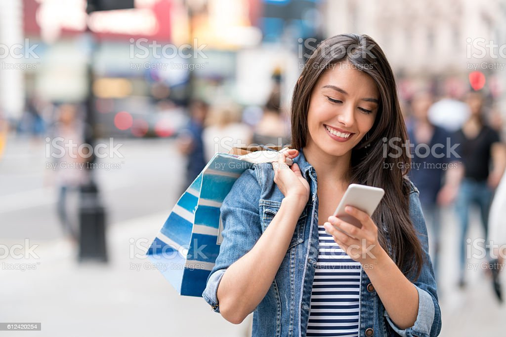 Shopping woman using app on her smart phone – Foto