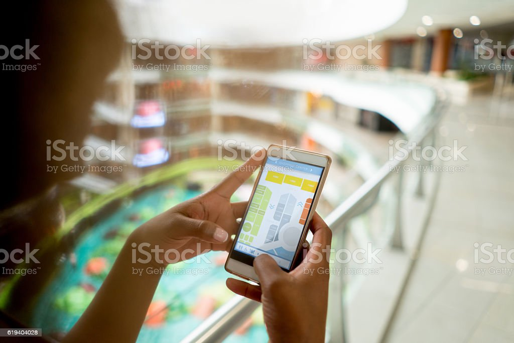 Shopping woman using her cell phone at the mall stock photo