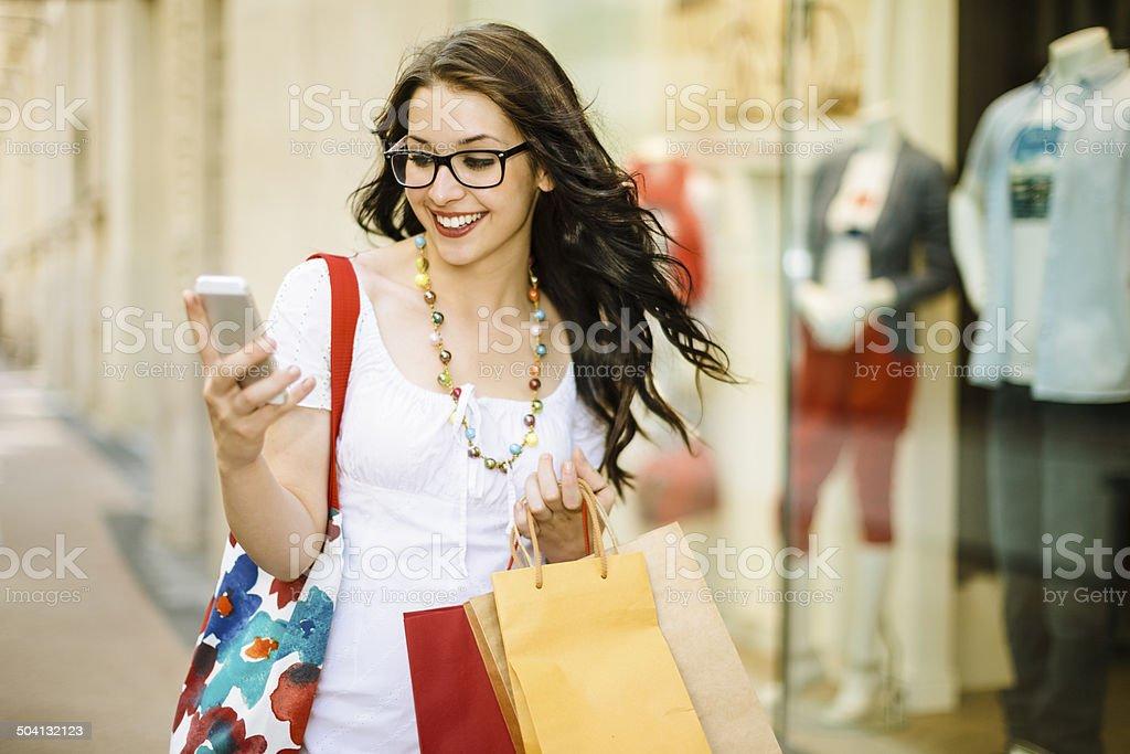 Shopping woman wearing glasses is texting downtown stock photo