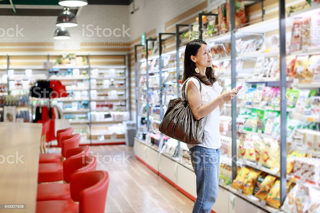 Shopping woman with cell phone stock photo