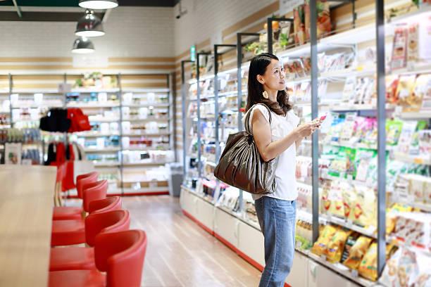 ショッピングの女性、携帯電話用 - スーパーマーケット 日本 ストックフォトと画像