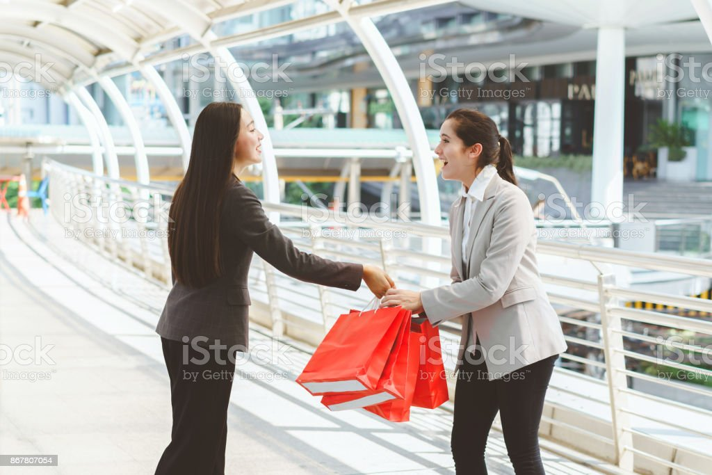 Shopping women send shopping bags to friends. Businesswoman send gift bags to colleague after promote & Shopping Women Send Shopping Bags To Friends Businesswoman Send Gift ...
