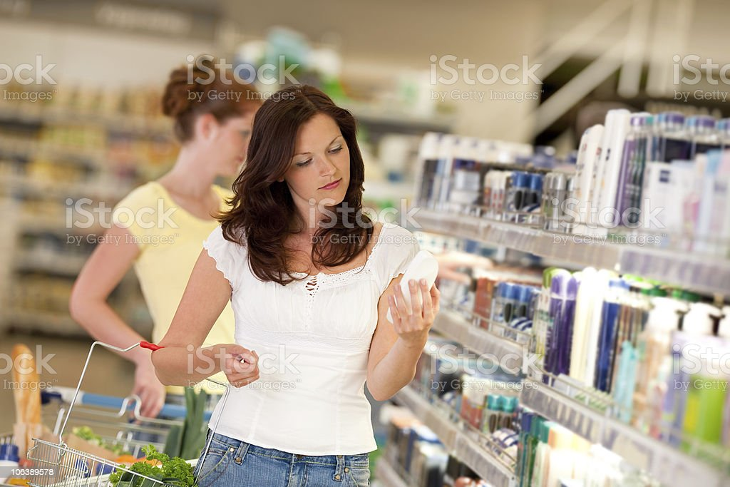 Shopping - Young woman with basket in supermarket stock photo