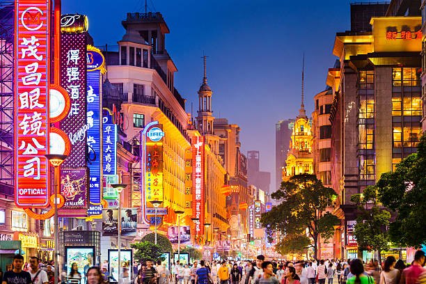 Shoppping Street in Shanghai Shanghai, China - June 20, 2014: Crowds walk below neon signs on Nanjing Road. The street is the main shopping district of the city and one of the world's busiest shopping districts. shanghai stock pictures, royalty-free photos & images