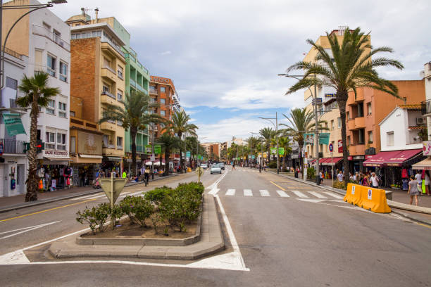 Shops and cafes near the narrow streets of Lloret de Mar. Downtown of Lloret, Spain. Tourists walking the streets of the city. – zdjęcie
