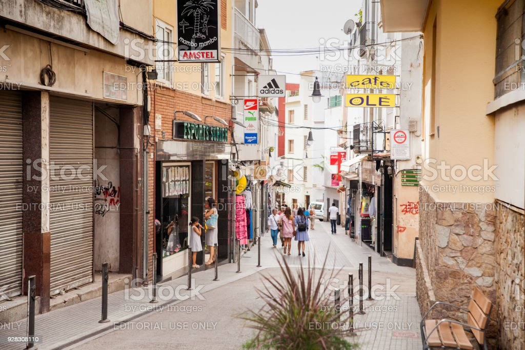 Shops and cafes near the narrow streets of Lloret de Mar. Downtown of Lloret, Spain. Tourists walking the streets of the city. stock photo