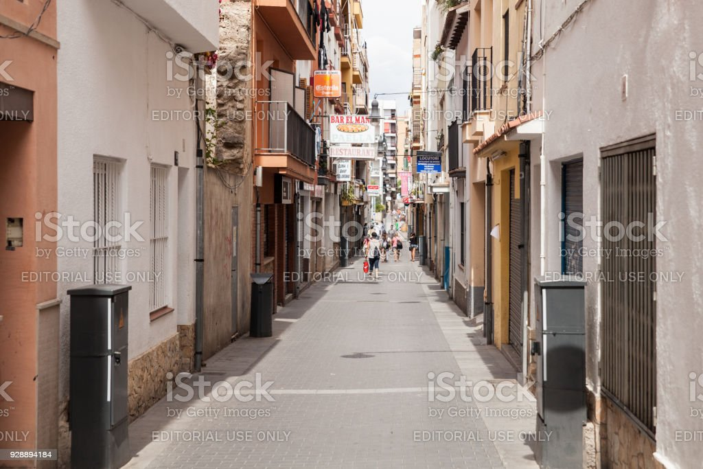 Shops and homes near the narrow streets of Lloret de Mar. Downtown of Lloret, Spain. Tourists walking the streets of the city. stock photo