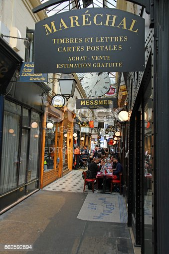 A covered passage in the Bourse District of Paris, it is filled with shops and lunch time diners.