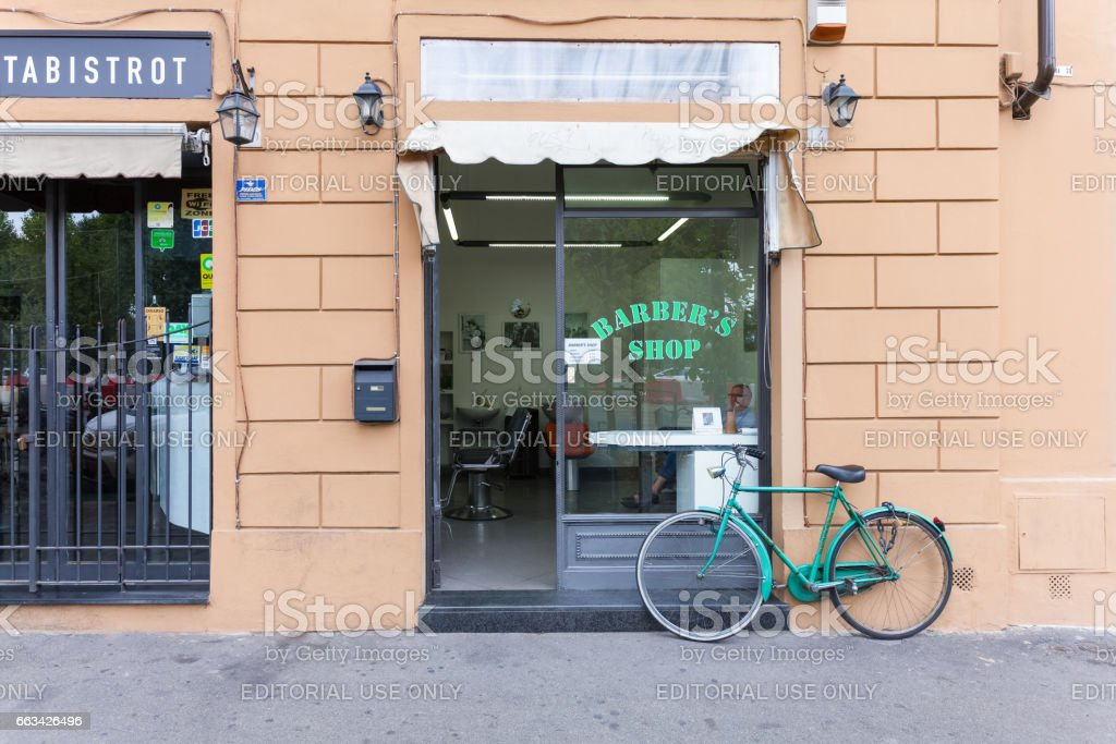 Florence, ITALY- September 10, 2016: Shop-window of barber shop with the barber (hairdresser) inside and bicycle parked near shop stock photo