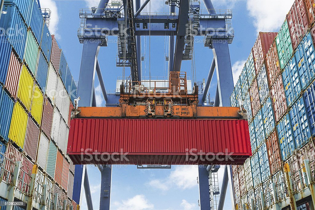 Shore crane lifts container during cargo operation in port stock photo