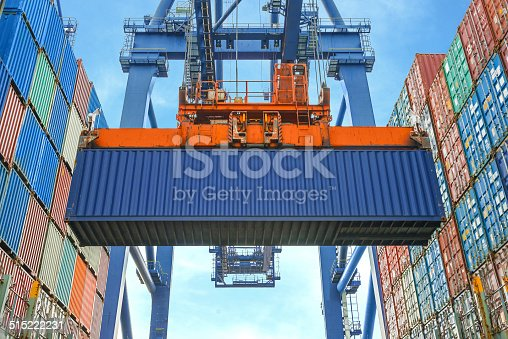istock Shore crane loading containers in freight ship 515222231