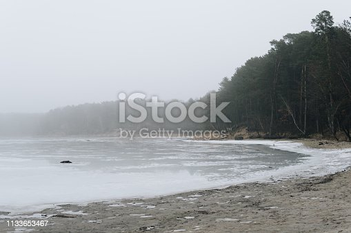 istock shore of a lake covered with ice and snow 1133653467