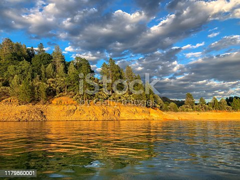 Beautiful horizon at Shasta Lake with pine trees, golden shores, reflections of water and a blue and cloudy day.
