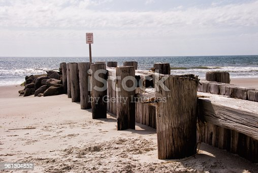Shoreline groin with a keep off sign at Pawleys Island Beach in South Carolina USA protects the nearby houses from the erosion of sand.