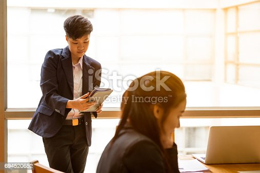 istock Short black hair asian business woman hold smart phone in hand in workplace with co-worker 694520652