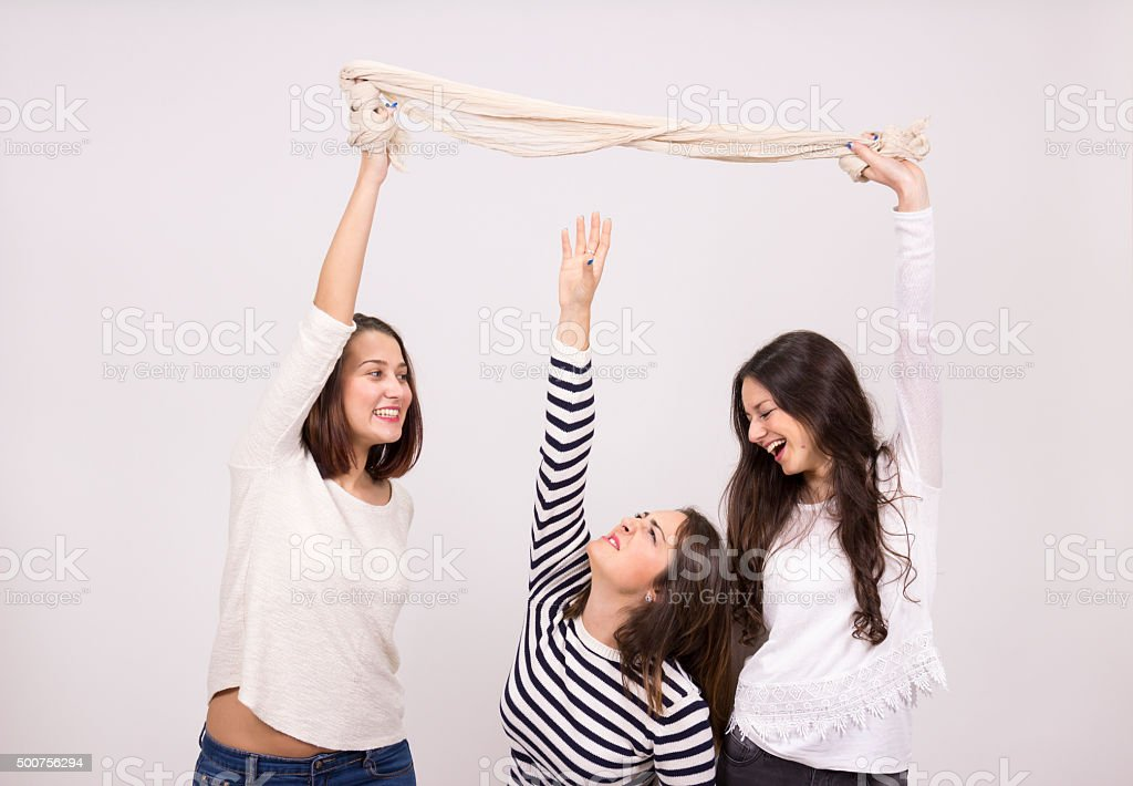 short girl trying to reach taller girls scarf stock photo