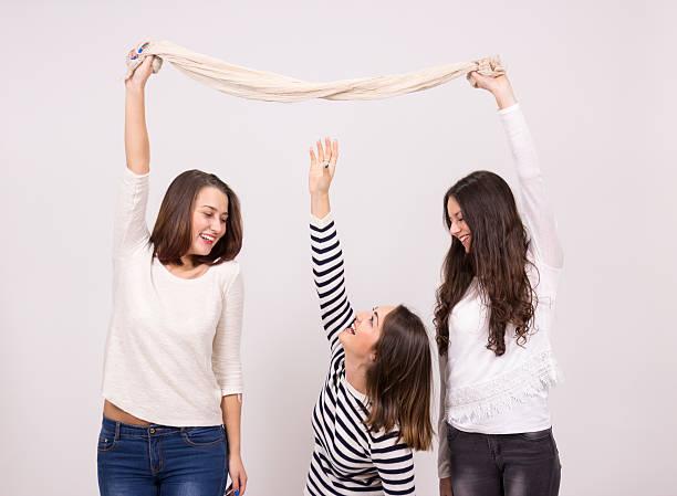 short girl trying to reach taller girls scarf - högväxt bildbanksfoton och bilder