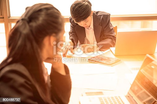 istock short hair asian business woman with teamwork work in office with laptop and smart phone on table,look at white paper in hand with concentrate face. 800488732