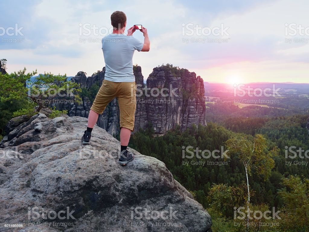 Short hair man on cliff takes photo. Sunny evening  mountains. foto stock royalty-free