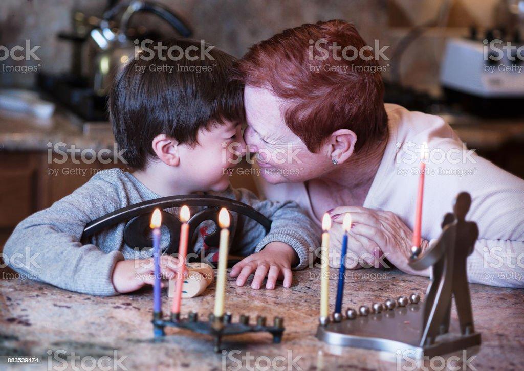短い髪赤い頭祖母と彼女の若い孫休日を楽しんでいたハヌカのろうそくの前に鼻をこする ストックフォト