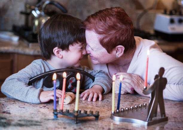 Short haired red head grandmother and her young grandson rub noses in front of the Hanukkah candles enjoying the holidays stock photo