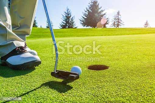 Golfer on the putting green preparing to tap his ball in