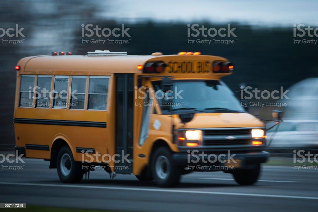 Short School Bus Driving Down A Street Stock Photo