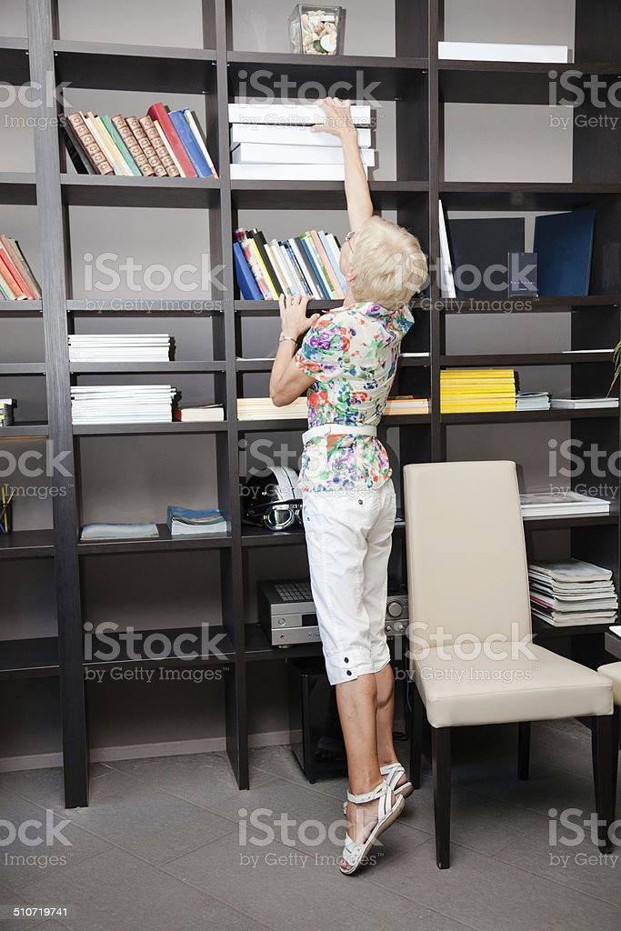 short senior woman stretches on tiptoe for documents in office stock photo