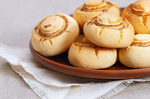 Shortbread cookies in form of champignons. Baked sweet biscuits on clay dishes with copy space. Delicious dessert.