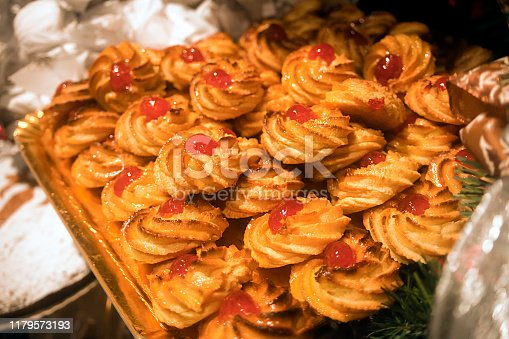 Shortbread tea cookies, traditional spanish pastry topped with candied cherries, retail display on a tray, high angle view. A Coruña, Galicia, Spain.