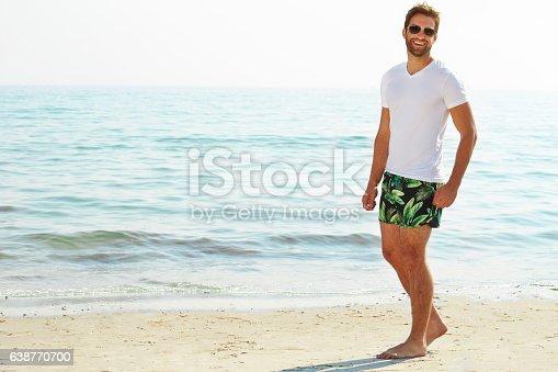 Shorts guy on beach smiling at camera