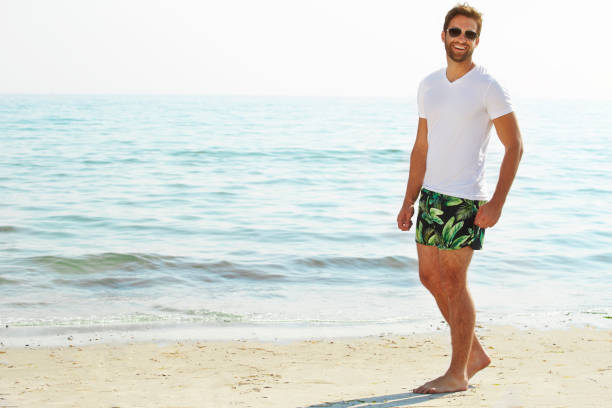 Shorts guy on beach Shorts guy on beach smiling at camera shorts stock pictures, royalty-free photos & images