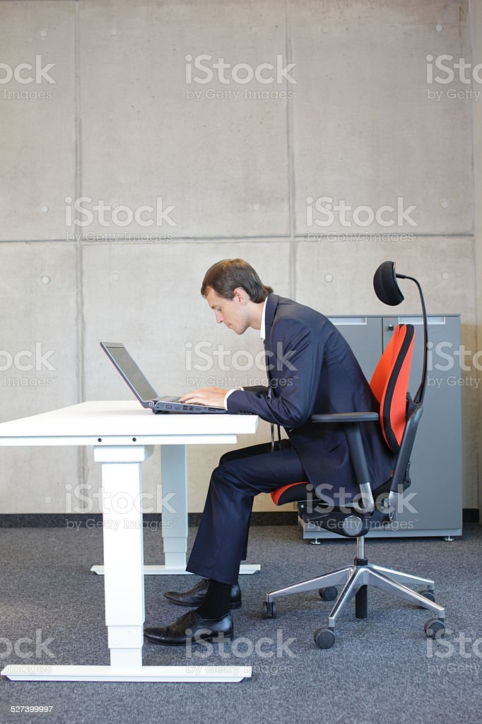 short-sighted business man bad sitting posture at laptop stock photo