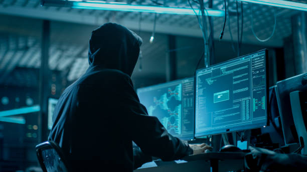 shot from the back to hooded hacker breaking into corporate data servers from his underground hideout. place has dark atmosphere, multiple displays, cables everywhere. - fragilidade imagens e fotografias de stock