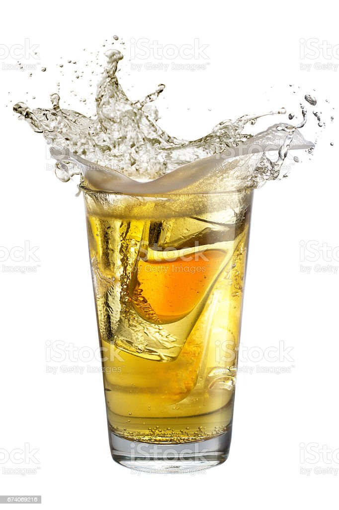 A shot glass filled with alcohol, placed inside a glass with beer. Splash royalty-free stock photo