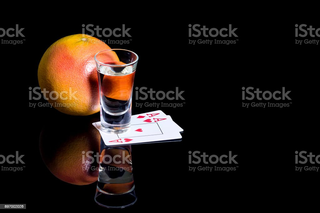 Shot glass of tequila with cards and Mandarin stock photo