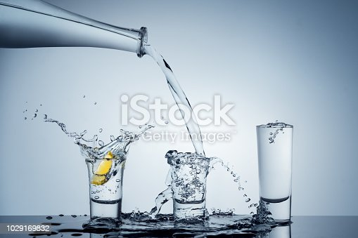 A messy pour of tequila/water into three shot glasses.