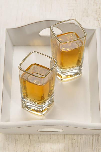 schnapsglas mit braunem rum - tablett holz stock-fotos und bilder