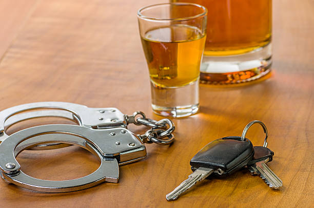 Shot glass with car keys and handcuffs stock photo